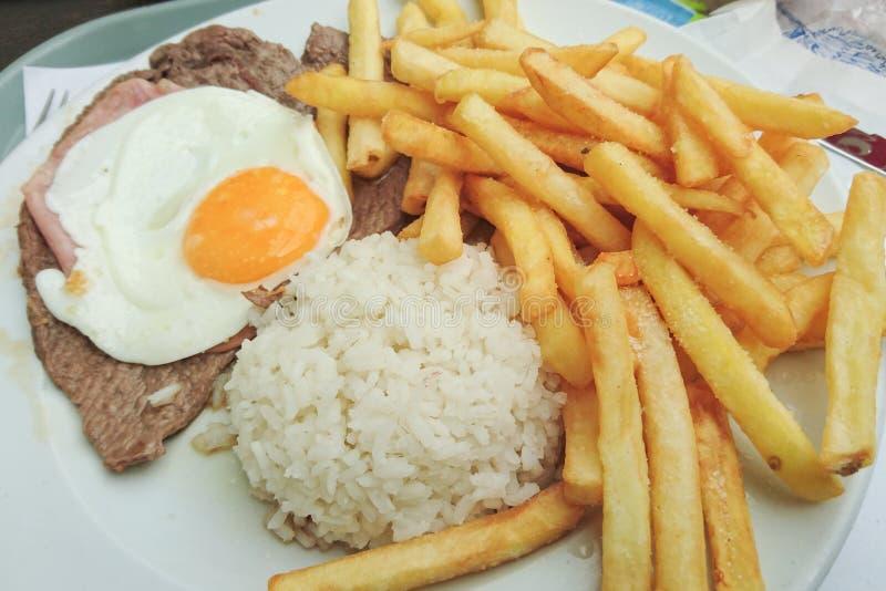 Comida portuguesa tradicional Prego ningún Prato con arroz, los microprocesadores, el huevo y la carne de vaca imagen de archivo libre de regalías