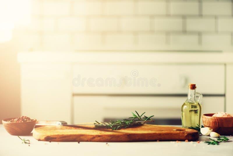 Comida que cocina los ingredientes en fondo interior del diseño blanco de la cocina con la tajadera de madera rústica en el centr fotografía de archivo libre de regalías