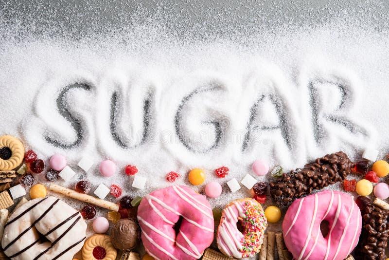 Comida que contiene el azúcar mezcla de anillos de espuma, de tortas y de caramelo dulces con la extensión y el texto escrito en  foto de archivo libre de regalías