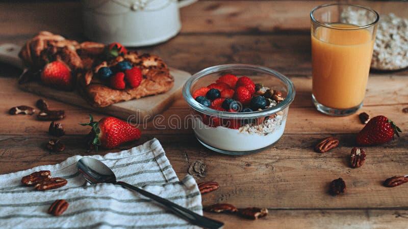 Comida que diseña el yogur dulce con la fruta en los tablones de madera imagenes de archivo