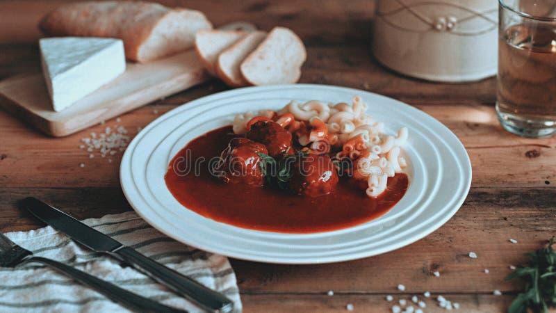 Comida que diseña la salsa de tomate con las pastas en los tablones de madera imagen de archivo