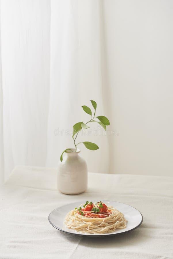 Comida, salsa bolo?esa de los espaguetis en el plato blanco y un florero de plantas en una tabla preparada blanca fotografía de archivo