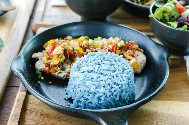 Comida sana, cerdo del ajo con el arroz azul, color azul hecho de b imagenes de archivo