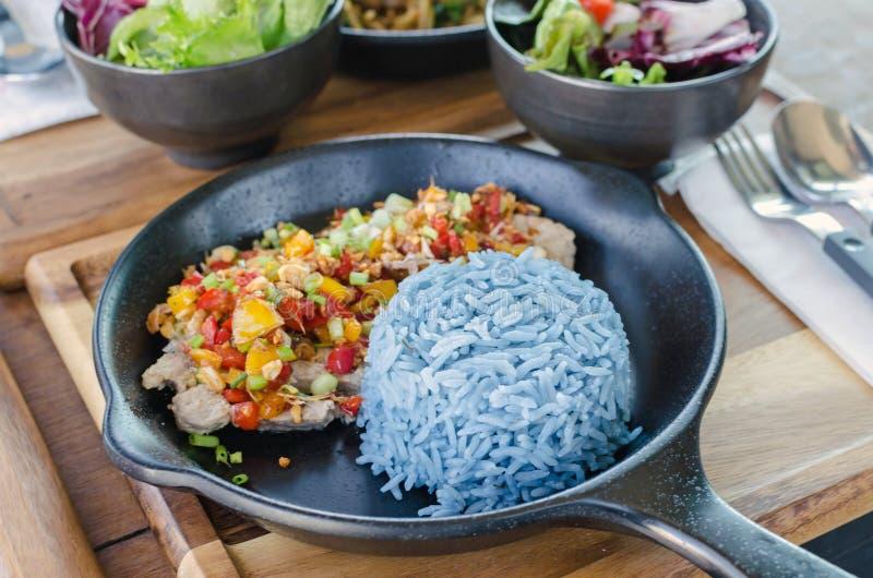 Comida sana, cerdo del ajo con el arroz azul, color azul hecho de b fotografía de archivo libre de regalías