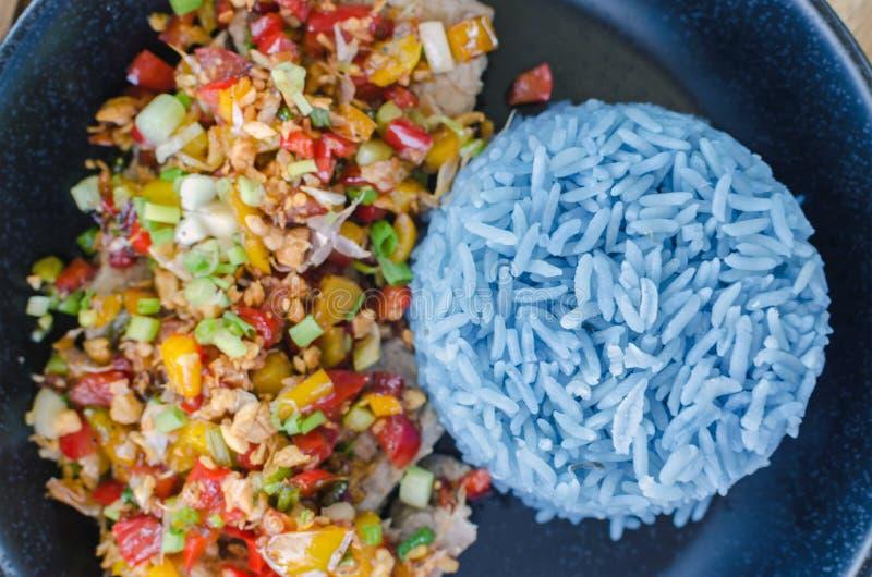 Comida sana, cerdo del ajo con el arroz azul, color azul hecho de b imagen de archivo