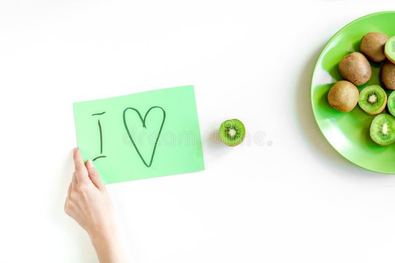 Comida sana con el kiwi en la placa en la opinión superior del fondo blanco del escritorio fotografía de archivo libre de regalías