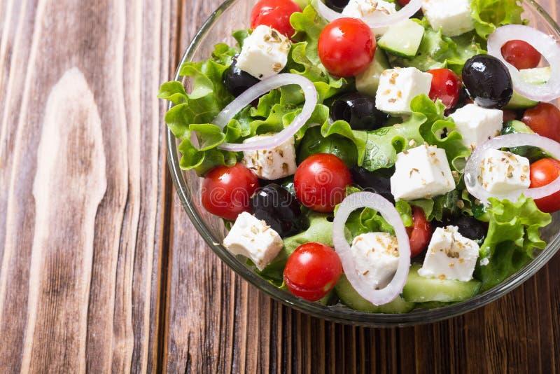 Comida sana de la ensalada griega de las verduras frescas en fondo de madera imagen de archivo