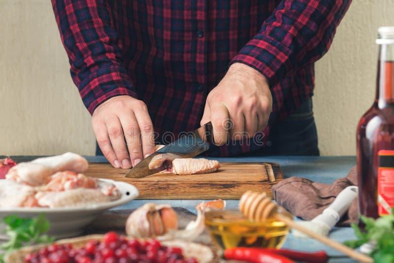 Comida sana de la preparación Hombre que cocina las alas de pollo con el cranber fotografía de archivo libre de regalías