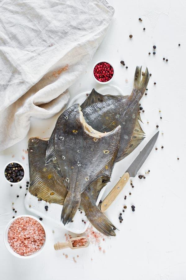 Comida sana dietética - platija, ingredientes para cocinar Fondo blanco, visión superior fotografía de archivo