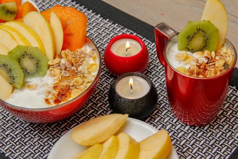 Comida sana, diversas semillas, cereales integrales y frutas secadas en yogur Fruta fresca, manzana, kiwi y caqui foto de archivo libre de regalías