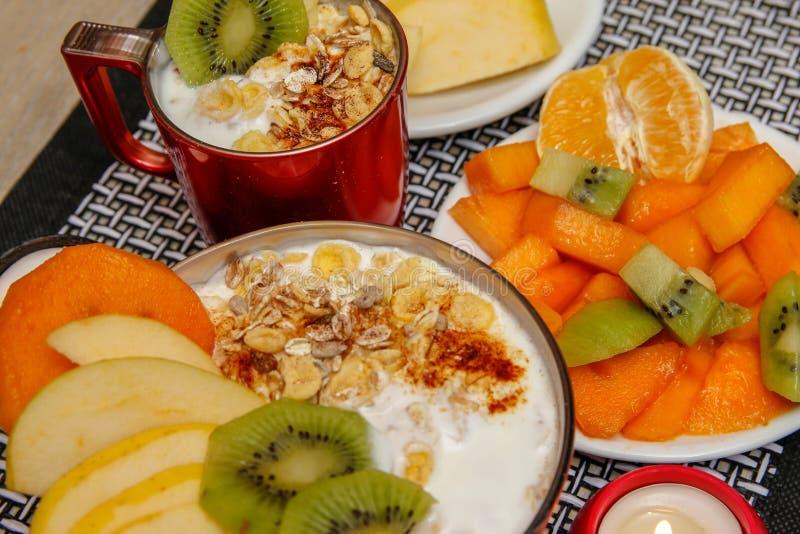 Comida sana, diversas semillas, cereales integrales y frutas secadas en yogur Fruta fresca, manzana, kiwi y caqui imagen de archivo libre de regalías