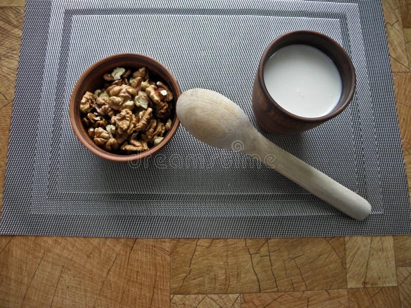 Comida sana en un plato marrón de la arcilla con una cuchara de madera en un mantel sobre un mantel gris foto de archivo