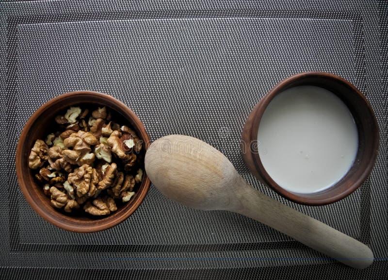 Comida sana en un plato marrón de la arcilla con una cuchara de madera en un mantel sobre un mantel gris foto de archivo libre de regalías