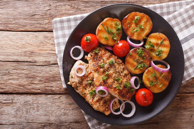 Comida sana: pechuga de pollo frita con las patatas y tom asados a la parrilla fotografía de archivo