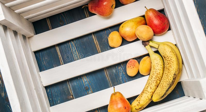 Comida sana: Plátanos frescos maduros, peras, albaricoques en la parte inferior de una caja de madera fotos de archivo