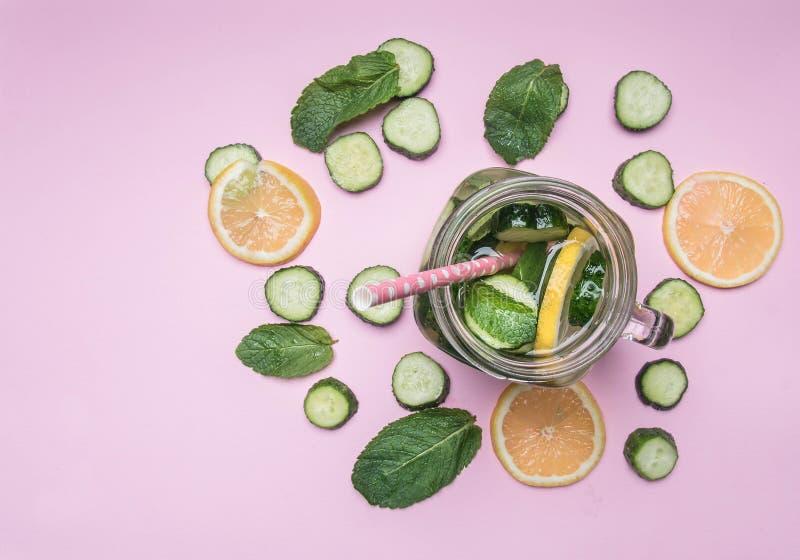 Comida sana, preparación de la limonada hecha en casa con el limón, pepino y menta, en endecha rosada del plano del fondo fotos de archivo