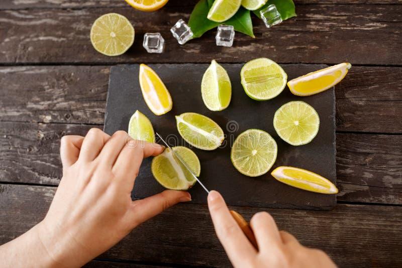 Comida sana y consumición mujer que corta los limones en tablero negro imágenes de archivo libres de regalías