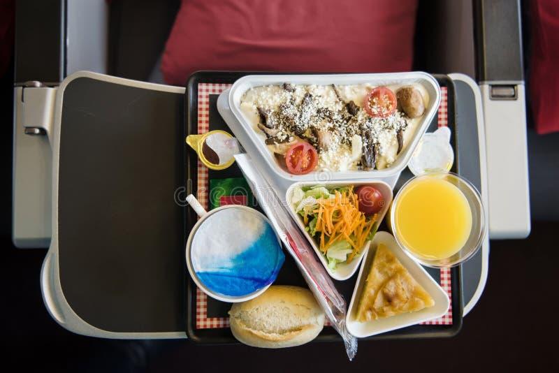 Comida servida a bordo del aeroplano en la tabla imagenes de archivo