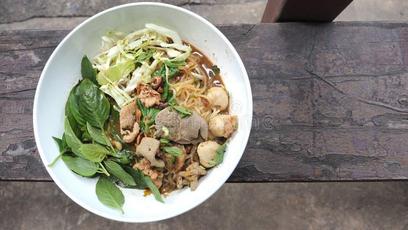 Comida tailandesa del cerdo de los tallarines del barco en la opinión superior de la foto de madera imagen de archivo