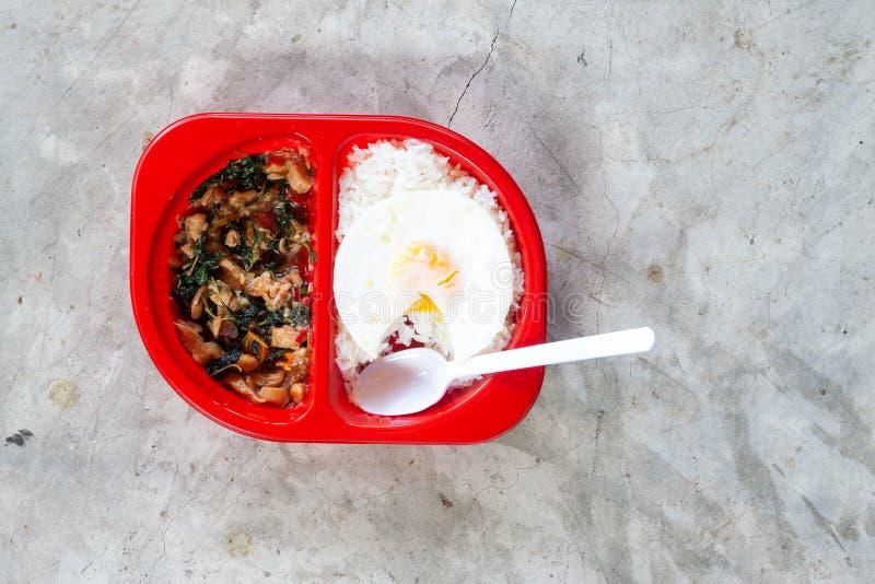 Comida tailandesa picante preparada con arroz y el huevo frito en fiambrera roja en fondo concreto fotos de archivo