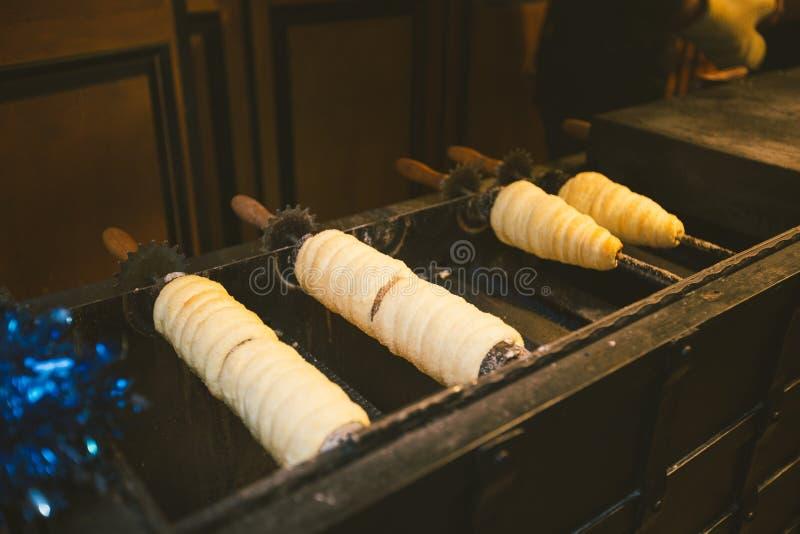 Comida tradicional de la calle de la República Checa del país Preparación de Trdelnik - panadería checa tradicional Los pasteles  imágenes de archivo libres de regalías