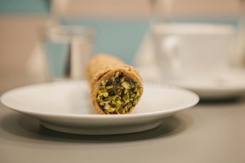 Comida tradicional dulce italiana Cannoli Pasteles frescos con el pistacho que llena dentro Cerca está una taza de café imágenes de archivo libres de regalías