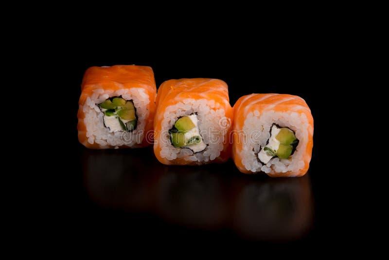 Comida tradicional japonesa - sushi con la cebolla del aguacate, del arroz, del requesón, de color salmón y verde en el fondo neg imagen de archivo libre de regalías