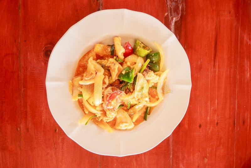 Comida tradicional tailandesa, calamar sofrito con el huevo salado en fondo de madera de la tabla imágenes de archivo libres de regalías