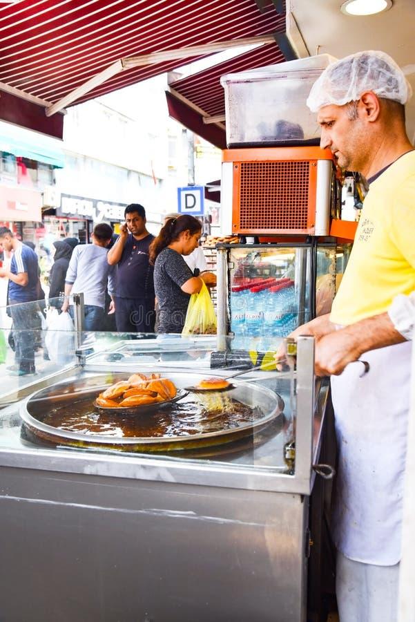 Comida tradicional turca de la calle como el postre frito del 'buñuelo 'con aceite, azúcar y jugo de uva levemente fermentado imagen de archivo