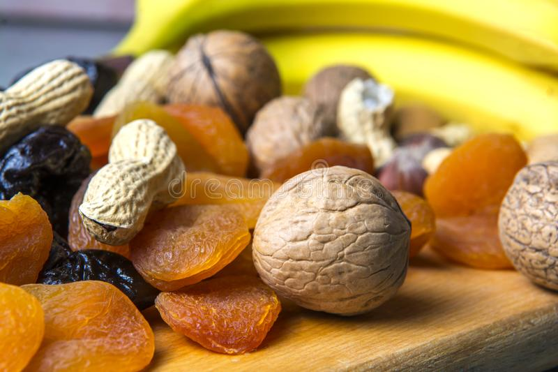 Comida vegetariana de nueces y de frutas secadas en el tablero de la cocina imagen de archivo