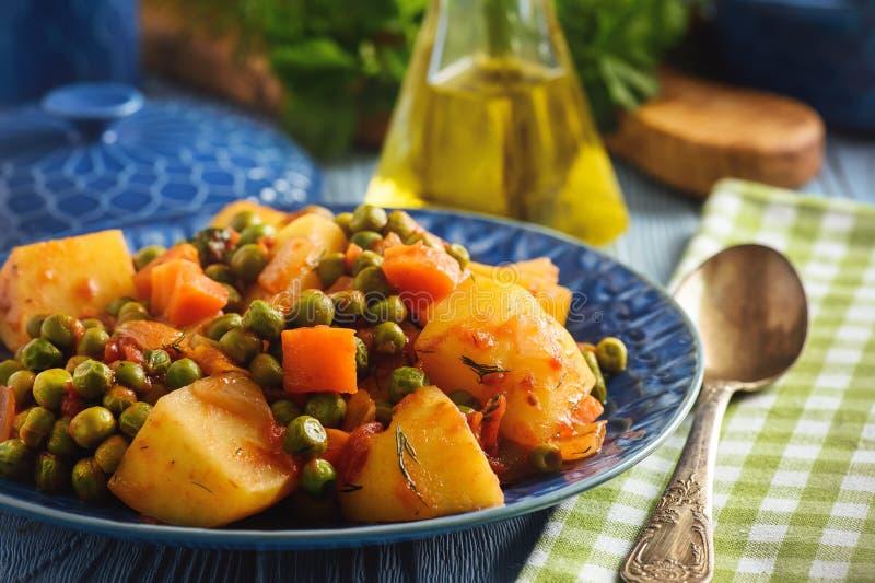 Comida vegetariana - patatas con el guisante y los tomates, cocina griega del estilo foto de archivo libre de regalías