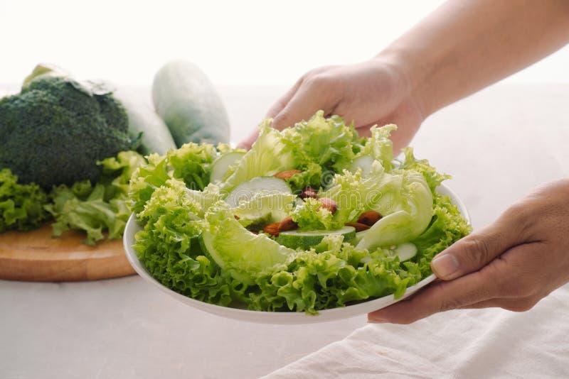 Comida verde del desayuno del vegano en cuenco con lechuga, el pepino, la cal y la almendra Placa con las manos visibles, visi?n  fotografía de archivo libre de regalías