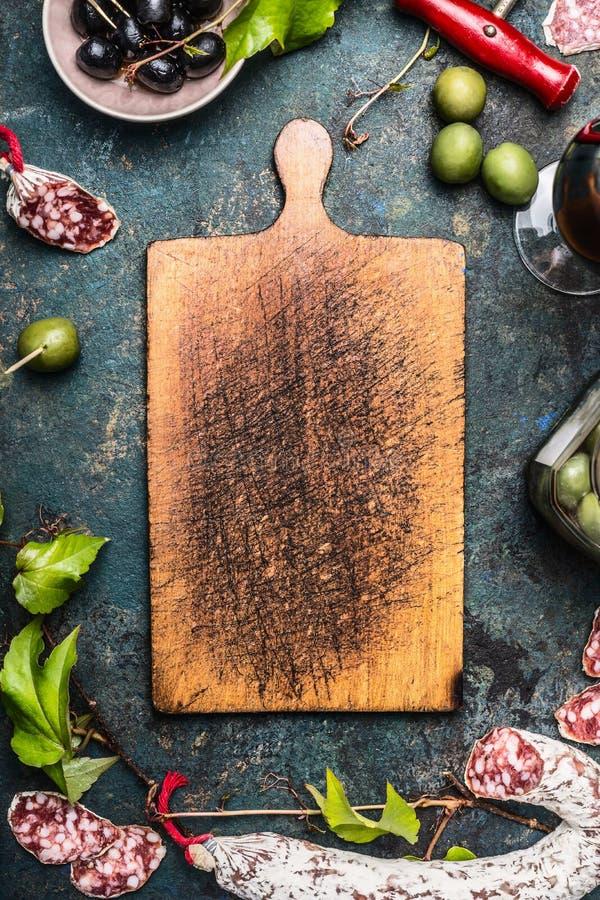 Comida y antipasti italianos alrededor de la vieja tabla de cortar de madera, visión superior fotografía de archivo