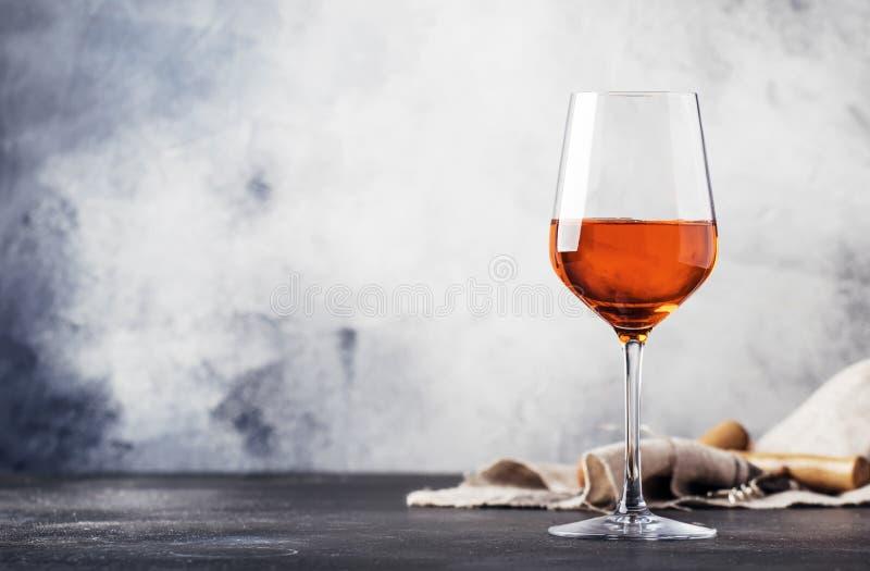 Comida y bebida de moda, vino anaranjado en el fondo de cristal, gris de la tabla, espacio para el texto, foco selectivo fotos de archivo