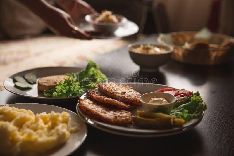 Comida y ensalada y patatas hechas en casa en la tabla fotos de archivo