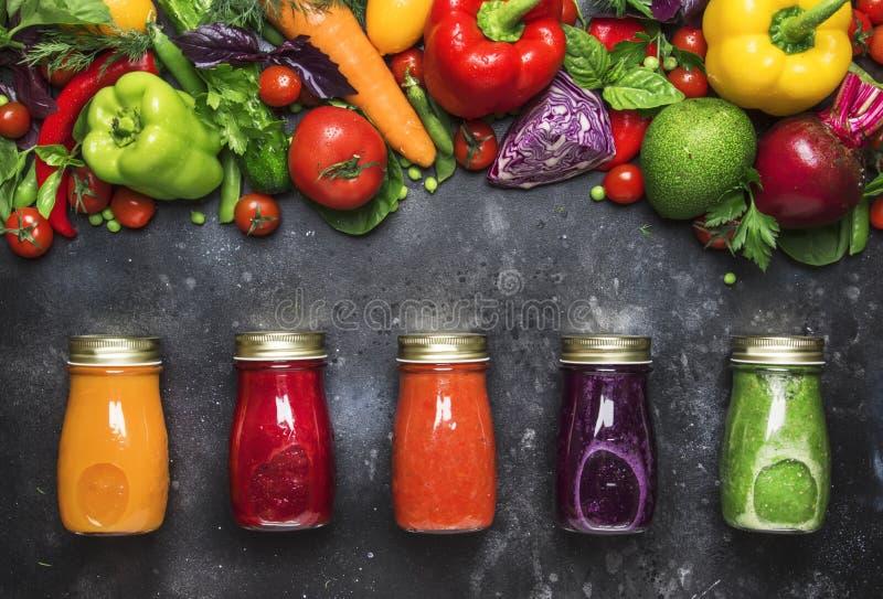 Comida y fondo de la bebida Jugos vegetales y smoothies del vegano colorido fijados en botellas en la tabla de cocina gris, espac imágenes de archivo libres de regalías