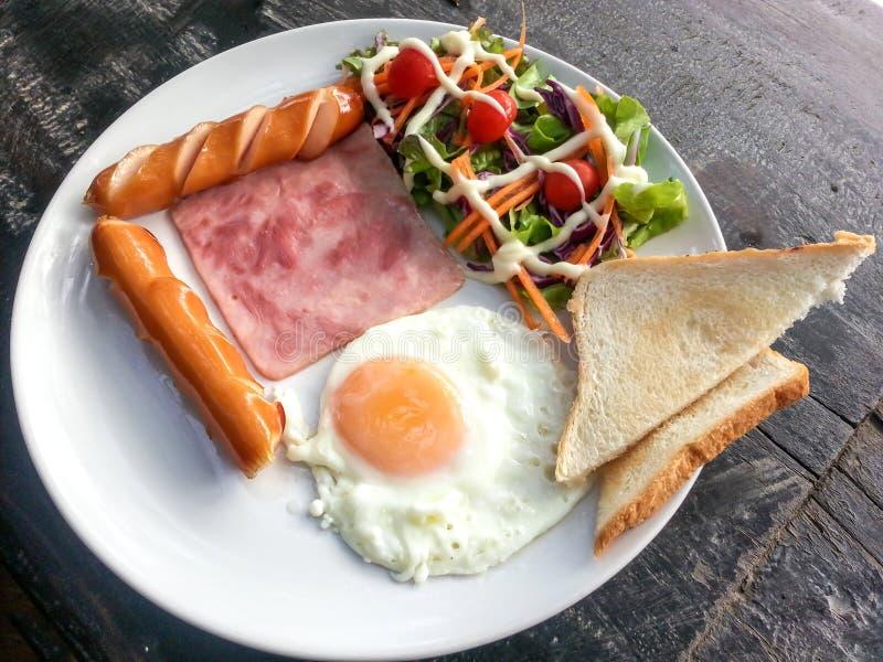 Comidas de desayuno - huevo frito, tocino, panes de las salchichas y vegetabl imagen de archivo libre de regalías