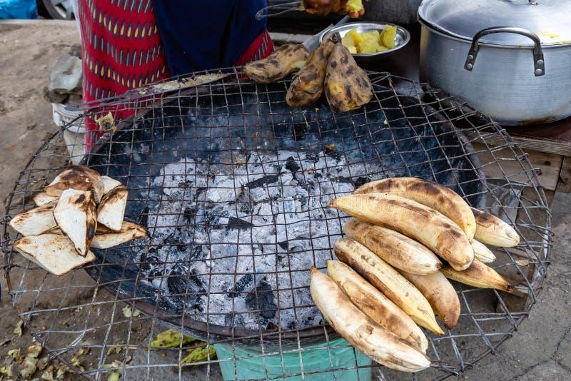 Comidas de la calle en Lagos Nigeria; Tronco conocido de otra manera como llantén asado, junto con el ñame y la patata dulce imagenes de archivo