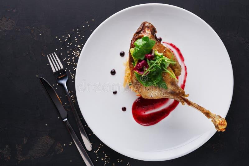 Comidas del restaurante Confit del pato con las verduras en fondo negro imagenes de archivo