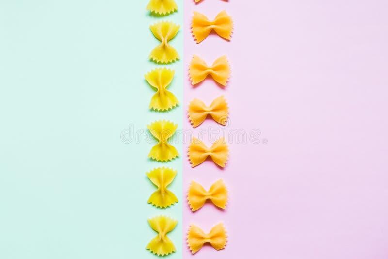 Comidas italianas concepto y diseño del menú Pastas crudas, Farfalle en el fondo blanco con endecha plana Composición con crudo imágenes de archivo libres de regalías
