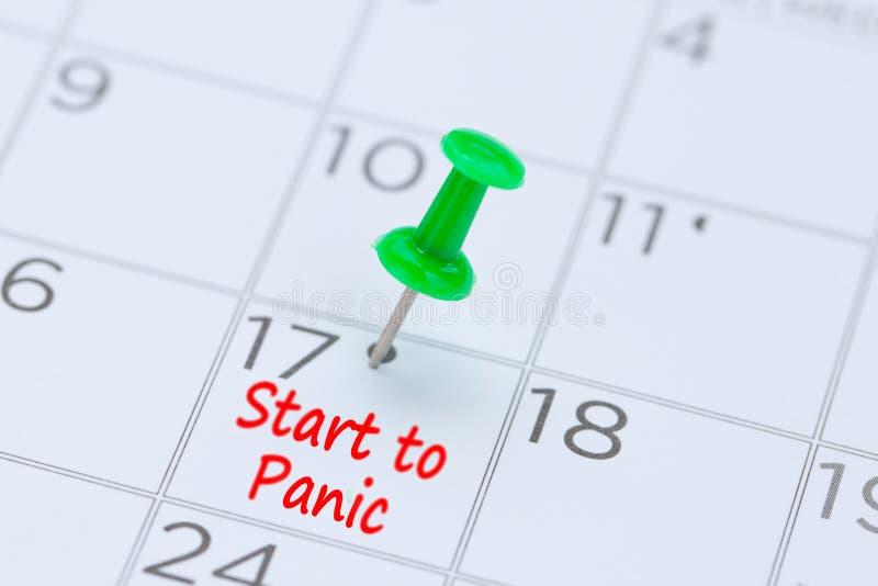 Comience al pánico escrito en un calendario con un perno verde del empuje a r imagen de archivo libre de regalías