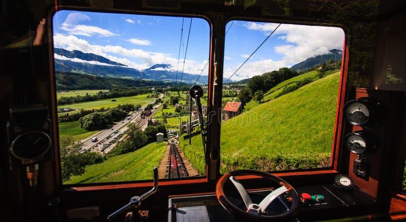 Comience su viaje y descúbralo que Suiza con el tren ferroviario suizo tradicional famoso vaga con paisaje alpino majestuoso imagen de archivo