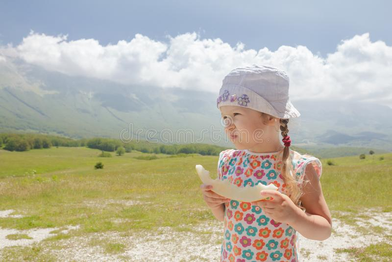 Comiendo el melón dulce corte a la niña que disfruta de la visión alpina imagenes de archivo
