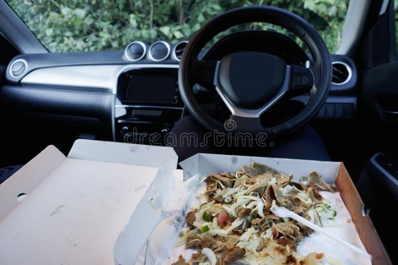 Comiendo la comida en el movimiento en el coche debido a la vida agotadora ocupada del trabajo que es malsana imagenes de archivo