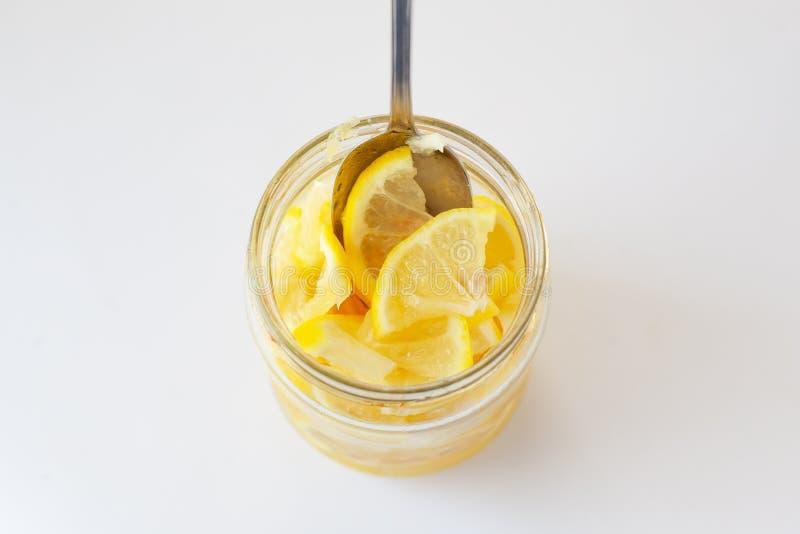 Comiendo los limones amarillos para aumentar inmunidad, limones cortados frescos en un tarro llenado del azúcar en el fondo blanc fotos de archivo libres de regalías