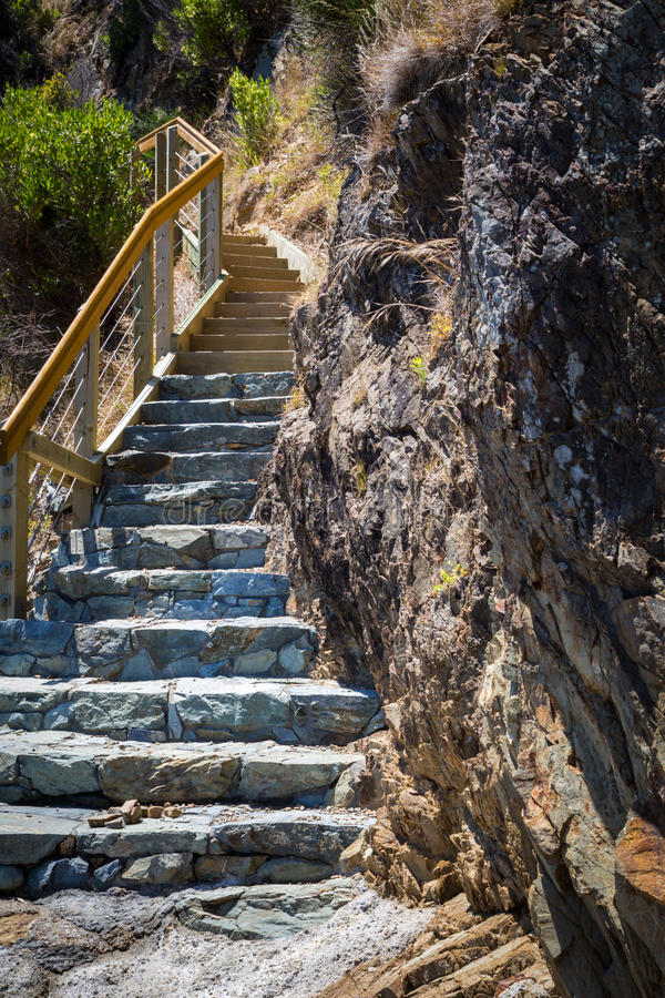 Comienzo de la escalera escarpada larga con los pasos de piedra en la costa foto de archivo