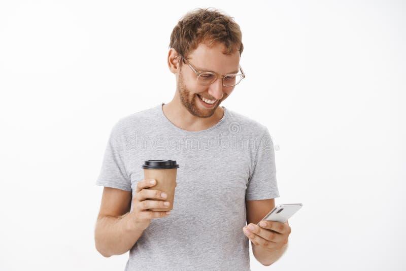 Comienzo de la mañana con bromas en Internet y café Retrato del individuo despreocupado feliz entretenido con la cerda que sostie imagen de archivo libre de regalías