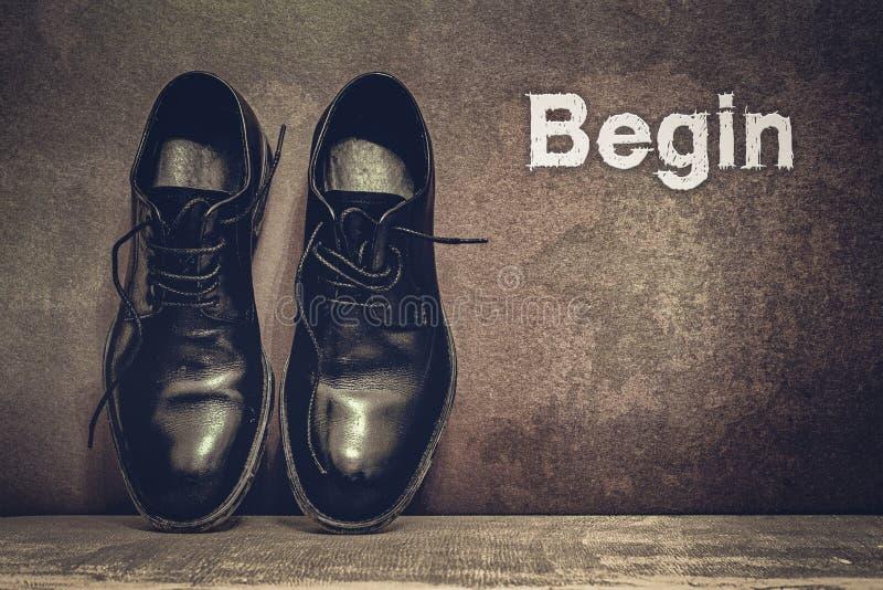 Cominci sulle scarpe marroni di lavoro e del bordo sul pavimento di legno fotografia stock