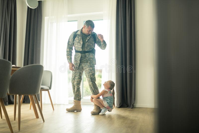 Serviceman calming his daughter down while coming back soon. Coming back soon. Loving serviceman calming his cute daughter down while coming back soon royalty free stock photo