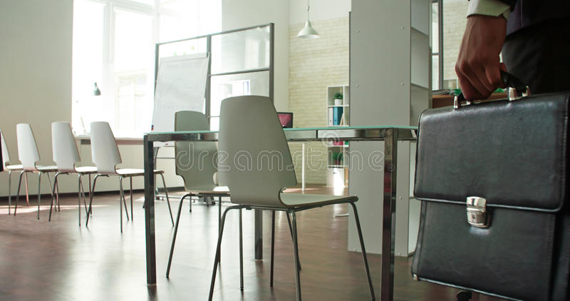 Coming businessman. Businessman entering empty board room stock images